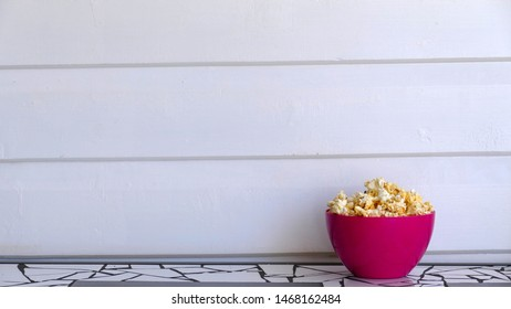Pink bowl of popcorn sitting on top of a table in front of a white weatherboard wall