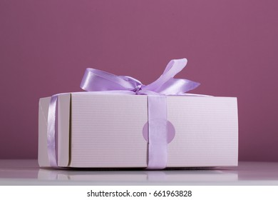 Pink box for cakes bandaged with ribbon on the table