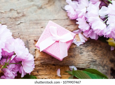 Pink box. Gift for woman. Top view.  Stately flowering Japanese cherry. Sakura. Flowering Japanese cherry. Green leafs. Weeding.