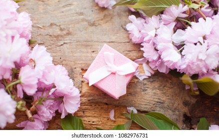 Pink box. Gift for woman. Top view. Stately flowering Japanese cherry. Sakura. Wooden table. Green leafs. Frame of white and pink flower on the white wooden table