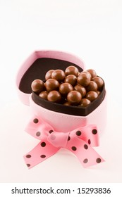 A pink box stuffed full of chocolates with a bow in front of it sits on a white background.