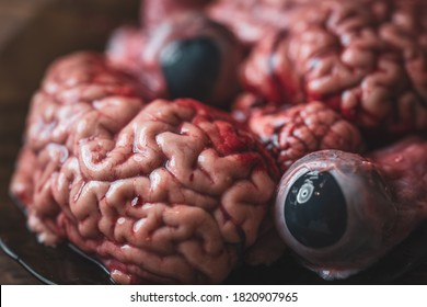Pink brain and eyeballs before cooking on a plate of dark glass stands on a wooden table. Raw fresh brain and eyes of a mammalian animal, a cow. Raw meat. Gut.