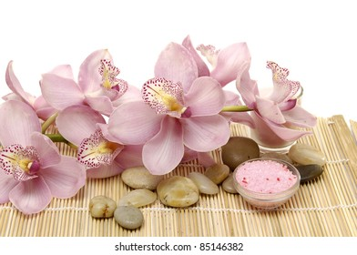 Pink branch orchid with bowl of sea salt and stones on mat