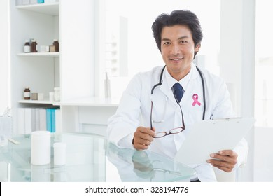 Pink breast cancer awareness ribbon against happy doctor sitting at his desk