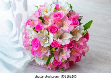 Pink bridal bouquet on wooden background