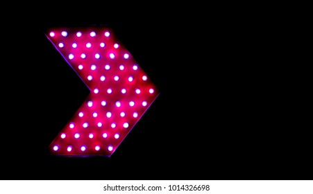 Pink bright and colorful illuminated display light bulb arrrow sign against black background