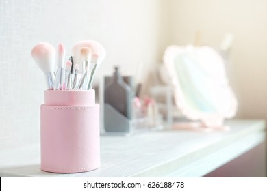 Pink brush set in package on cosmetic table for makeup. Dressing table. Cosmetic Composition. Make up table concept. Flat lay, front view.