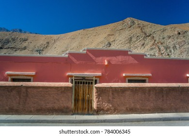 Pink building in Pisco Elqui in Paihuano, Coquimbo Region, Chile near La Serena & Santiago during fall foilage. Striking blue sky from dry air & clear sky in the Andes mountain.