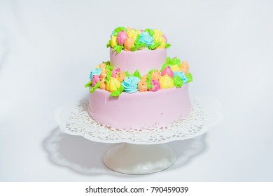 pink cake with flowers made from mastic on a light background