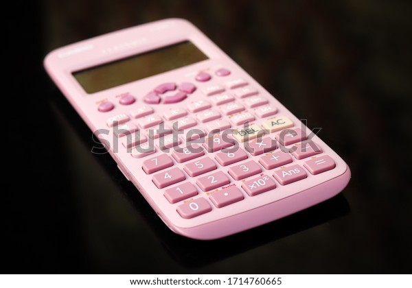 A pink calculator on a table