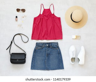Pink cami top, blue denim mini skirt, straw boater hat, sunglasses, black cross body bag, white sneakers, jewelry on grey background. Woman's casual outfits. Flat lay, top view. Trendy summer look.