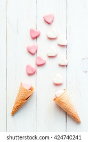 Pink candies in ice cream cone. Creative candies on wooden white background. Top view,  flat lay