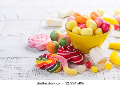 Pink candies, lollipops and jelly beans on white wooden background. Sweet greeting card. Copy space. Top view