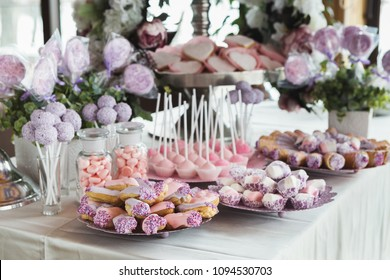 Pink candy bar for holiday celebration. Sweet buffet for birthday party or wedding. Desserts assortment against wooden background, catering concept