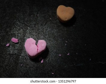 Pink candy heart broken in two on dark textured background