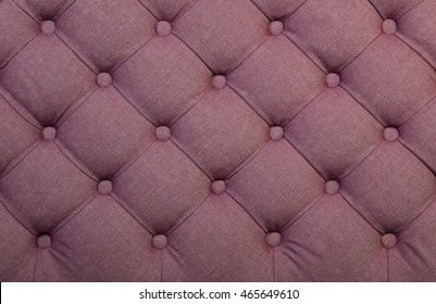 Pink capitone textile background, retro Chesterfield style checkered soft tufted fabric furniture decoration with buttons, close up