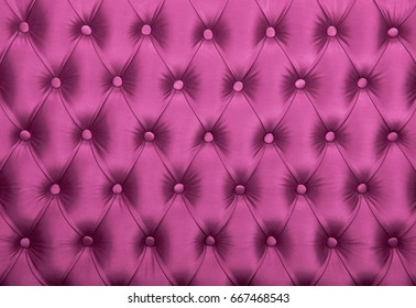 Pink capitone textile background, retro Chesterfield style checkered soft tufted fabric furniture diamond pattern decoration with buttons, close up