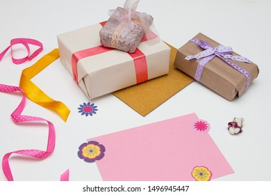 pink card paper and beautiful gifts on a white background Thanksgiving, birthday, mother's day, copy space,paper flowers,ribbon and bows decor