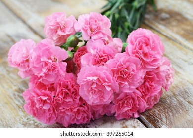 Pink carnation bouquet on rustic wooden surface, closeup