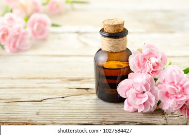 pink carnation flowers and essential oil on the wooden board