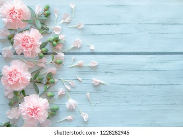 pink carnation flowers on wood table.