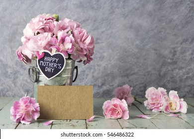 Pink carnation flowers in zinc bucket with happy mother,s day letter on wood heart and blank brown card