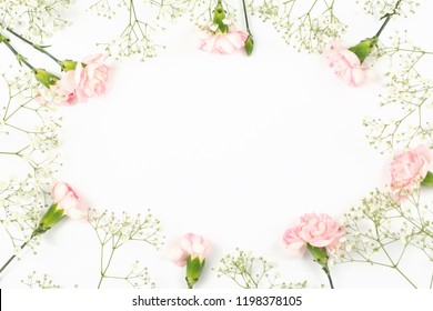 Pink carnation and gypsophila pattern on the white background. Flower concept. Copy-space for your text. Top view, flat-lay.