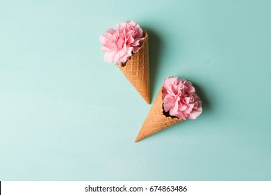 Pink carnations in waffle cones on a green background.