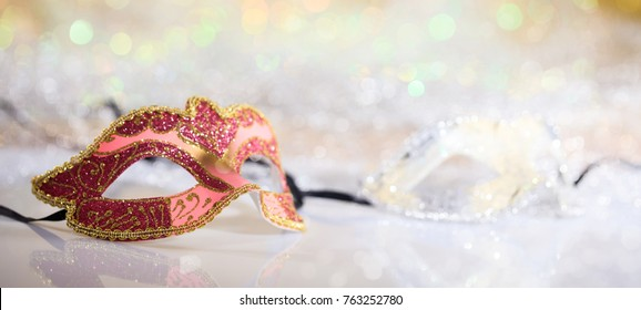 Pink carnival mask on white surface, abstract bokeh background