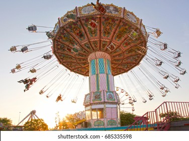 a pink carousel ride spins fast in the air in florida at sunset