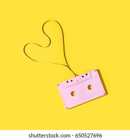 Pink cassette tape on a yellow background