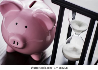 Pink ceramic piggy bank with an hour glass, conceptual of time running out to save for your retirement, a nest egg or to meet your dreams