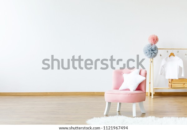 Pink chair with star shaped cushion standing in bright baby room interior with wooden hanger with pompoms. Paste your product here