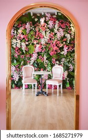 Pink chair. A table and pink vintage chair with beautiful pink and purple orchid flowers wall on the background.