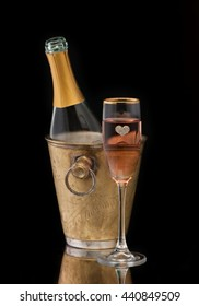 Pink Champagne in a bucket and a glass of champagne, vertical