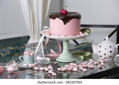 Pink Cherry Cake Topped with Chocolate Ganache on Cake Stand Surrounded by Peppermint Candies on Glass Table with Polka Dot Tea Pot
