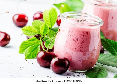 Pink cherry milkshake or smoothies with fresh berry and chia seeds, white stone kitchen background, place for text, top view