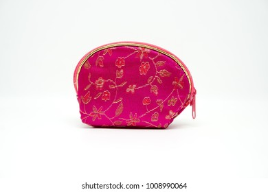 Pink Chinese coin purse with gold floral embroidery on white isolated background.