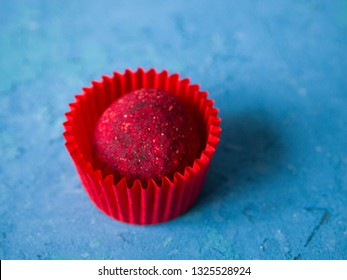 Pink chocolate truffle in a red candy wrapper on a blue concrete background. One delicate bright raspberry truffle.