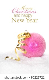 Pink christmas ball with gold ribbon bow on a snow  (with sample text)