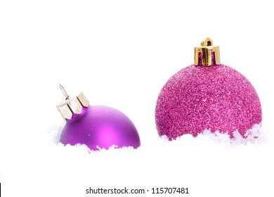 pink christmas ball ornaments lying in snow