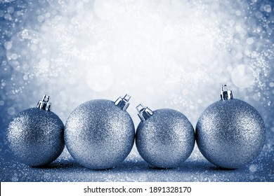 Pink Christmas baubles on silver glitter with defocused lights on background, New Year greeting card. Blue classic tone