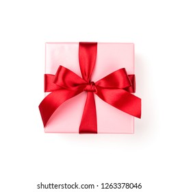 Pink Christmas gift box tied with red ribbon bow isolated on white background. Top view.