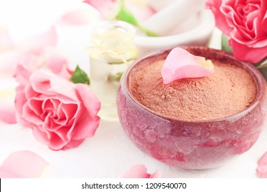 Pink clay powder in bowl for making face mask, holistic beauty treatment and skin care, fresh rose petals essential oil. Close up with soft light. Delicate skin cleanser