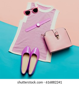 Pink clothes and accessories. Top view. Top, shoes, watches and sunglasses. Stylish bag. Summer trend