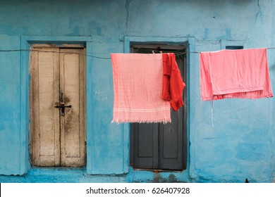 Pink clothes hanging in front of bright blue texture background with doors in Bangalore, India