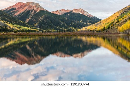 Pink clouds reflected in Crystal Lake below the Red Mountains in Autumn in the Uncompahgre National Forest south of Ouray, Colorado.