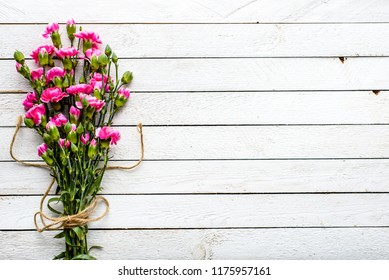 Pink cloves, spring flowers bouquet, overhead on white wooden background with copy space