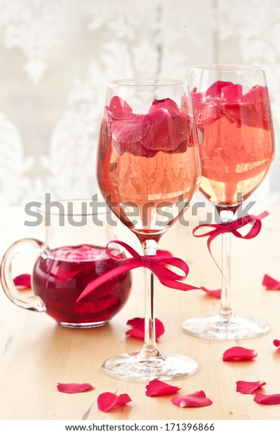Pink Cocktail with fresh rose petals on wooden table
