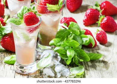 Pink cocktail with strawberry, basil, gin and ice, wood background, selective focus